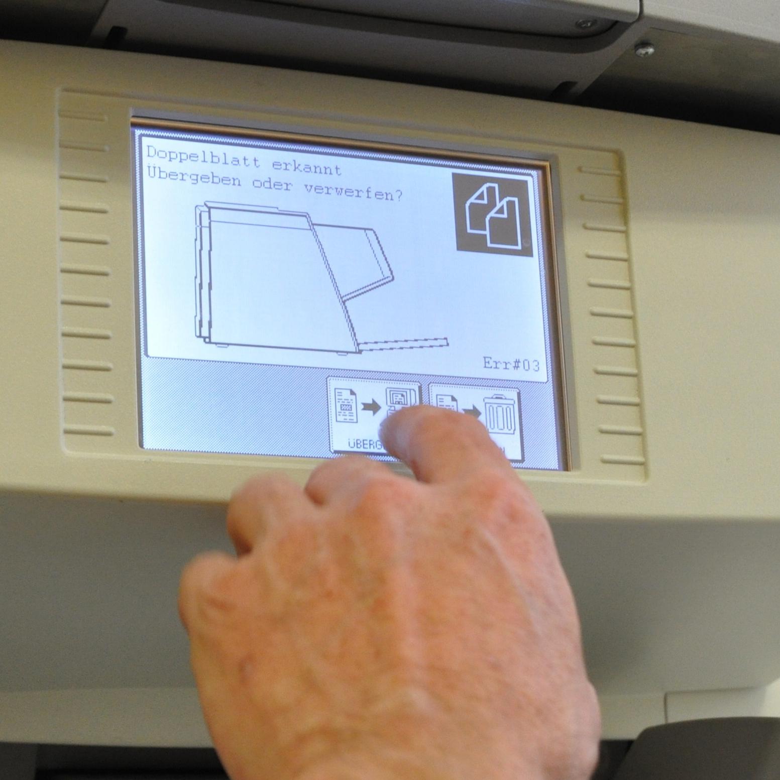 Hand zeigt auf Display eines Aktenscanners